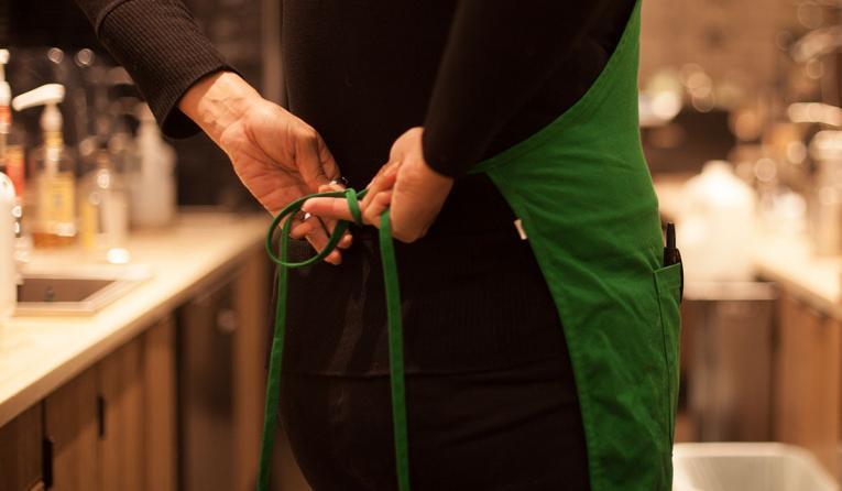 Starbucks employee ties their apron.