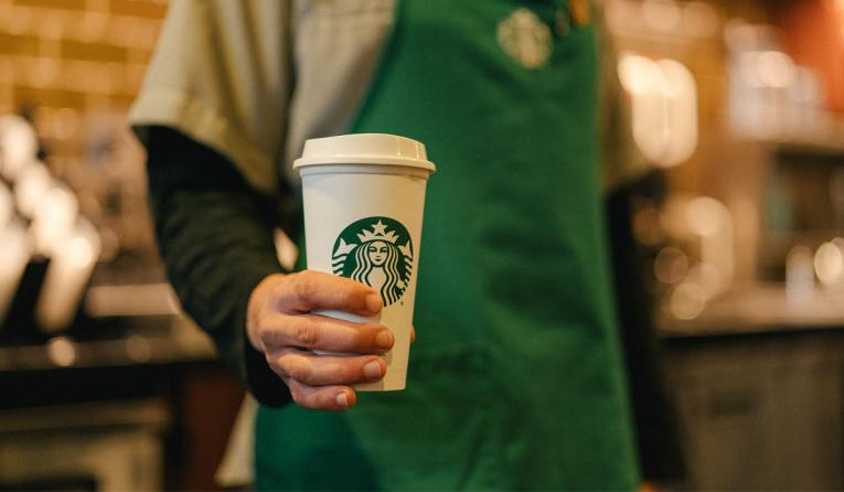 Starbucks employee holding a cup.
