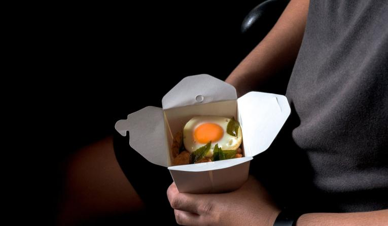 Takeout box of food with an egg in it.