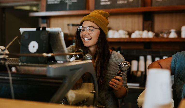 A barista punches in an order on a digital device.