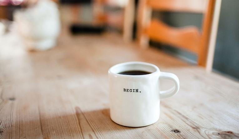 "Coffee mug with the words ""begin' on the front."