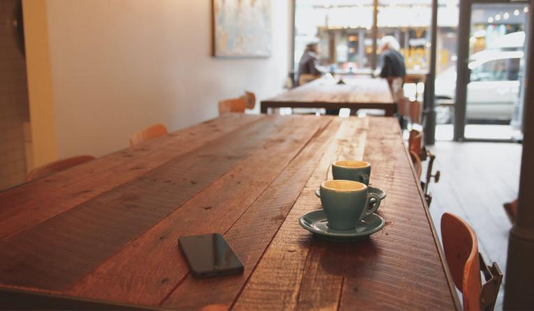 Wooden table with two cups of coffee on it.