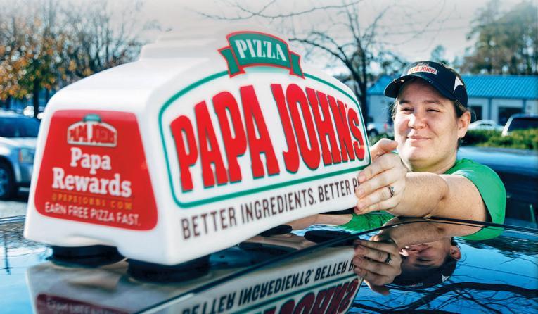 Woman installing Papa John's sing onto a car