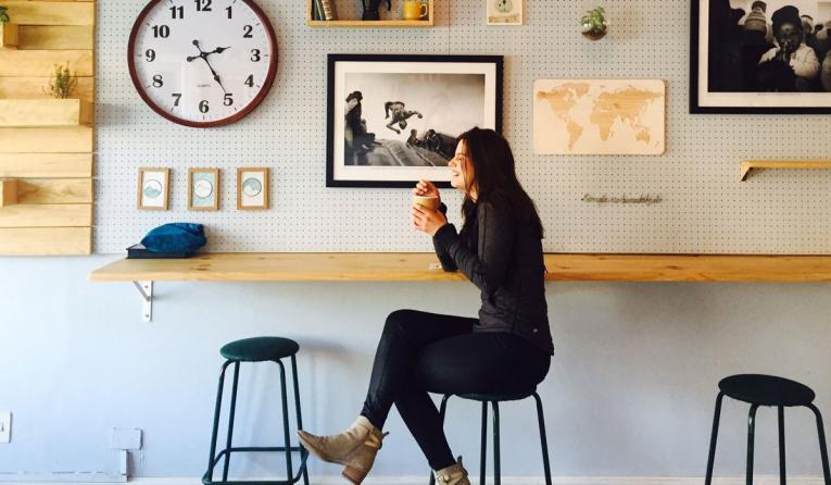 A customer enjoys a cupe of coffee inside a cafe.