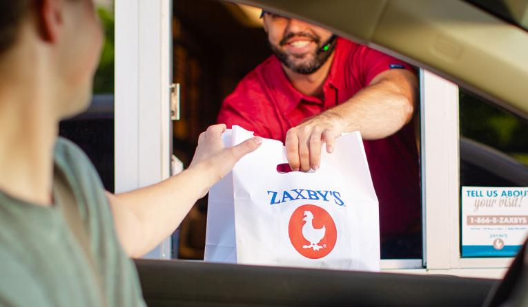 Zaxby's employee hands a customer food through the drive thru.