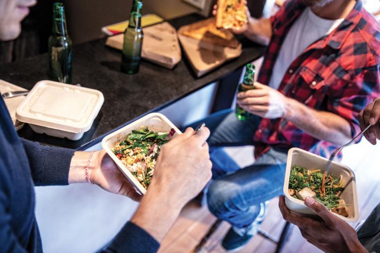 Three men eating take out food