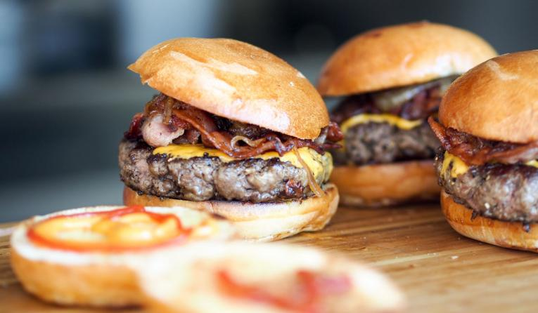 Burgers on a wooden table.