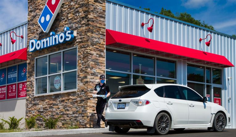 Domino's employee brings pizza to a car.