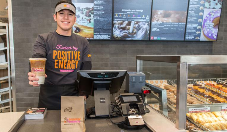 Dunkin' employee holds out a cup of coffee.