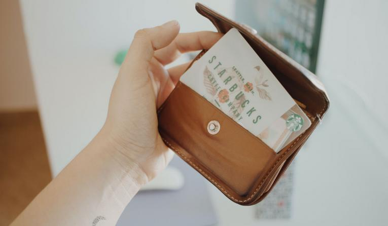 Starbucks loyalty card held by customer.