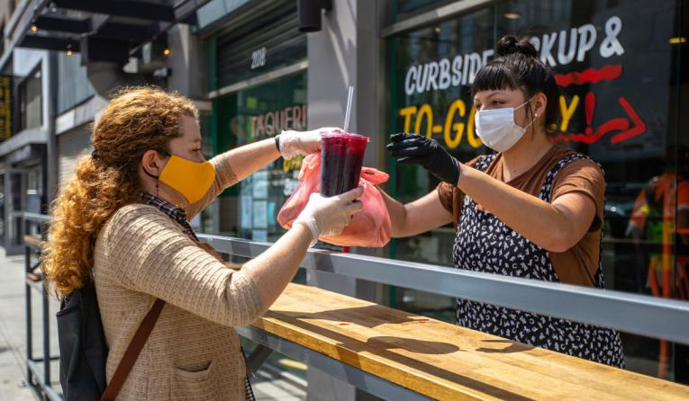 Restaurant owner hands an order to a customer outside the restaurant; they are both wearing gloves and masks