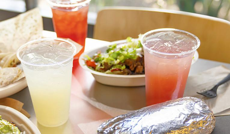 Chipotle food with sparkling drinks on table.