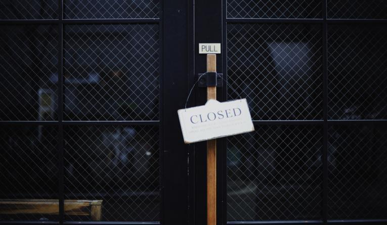 Closed sign hands outside a door.