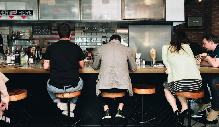Restaurant goers sit at stools in front of a counter.