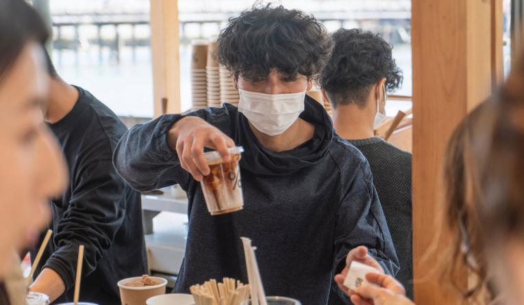 Customer with a mask grabs a cup of coffee.