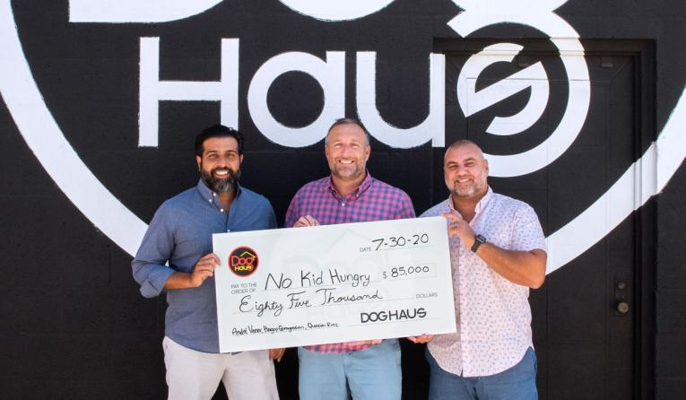 Dog Haus presenting a check.