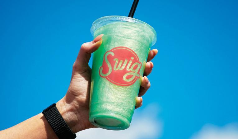 Hand holding Swig beverage