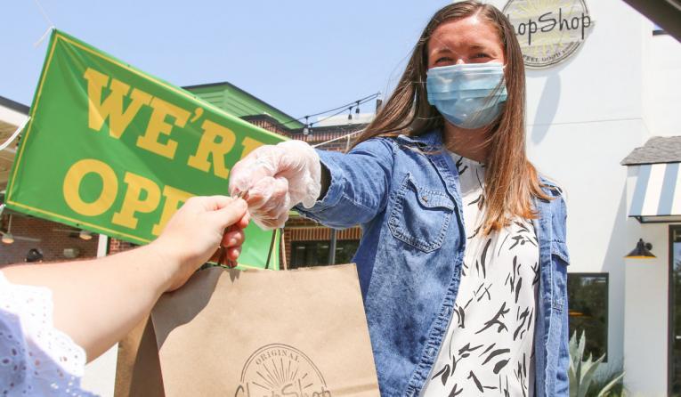 Original ChopShop employee wearing a mask handing out food to customer.