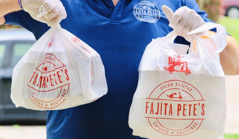Fajita Pete's to-go orders in bags being carried by an employee.