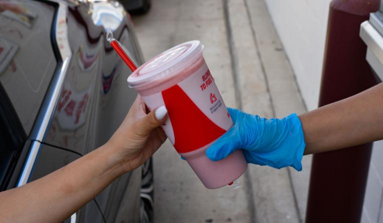 Smoothie King employee hands a customer a smoothie through the window of a drive thru.