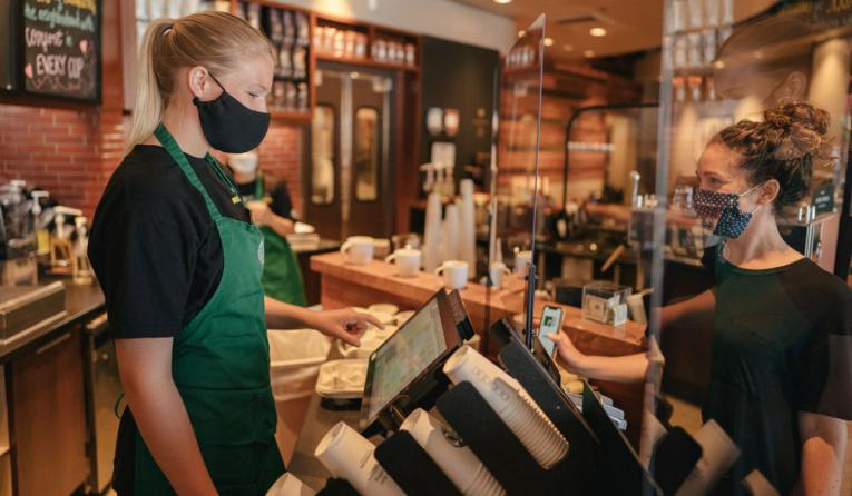 Starbucks employee with a mask serves a customer.