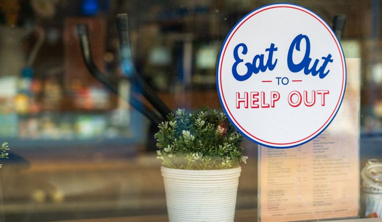 """Eat out to help out"" sign on the window of a restaurant."