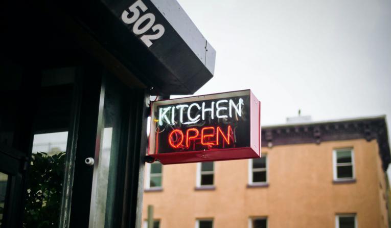"""Kitchen Open"" sign hangs outside a restaurant."