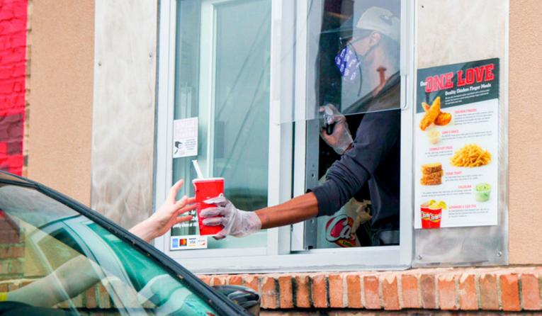 Raising Cane's drive-thru employee hands food out the window.