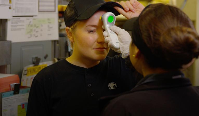 A Taco Bell employee gets their temperature taken.