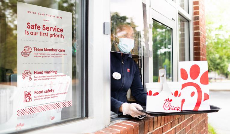 Chick-fil-A employee at the drive thru window handing out food.