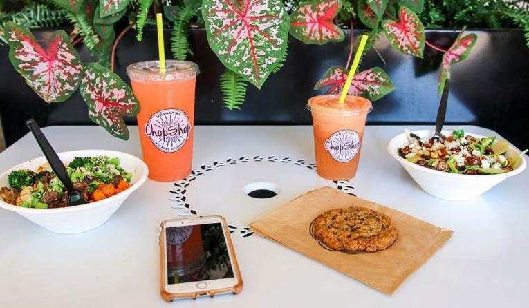 Original ChopShop food with drinks and a phone.