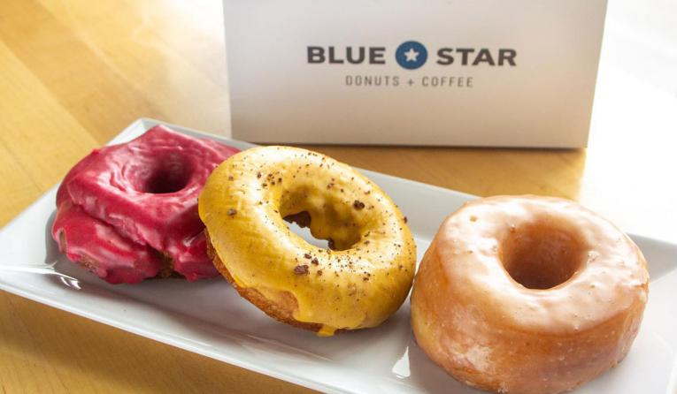 Blue Star Donuts in a row with a box behind them.