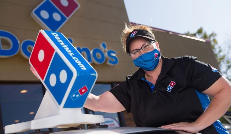 Domino's employee near a car.
