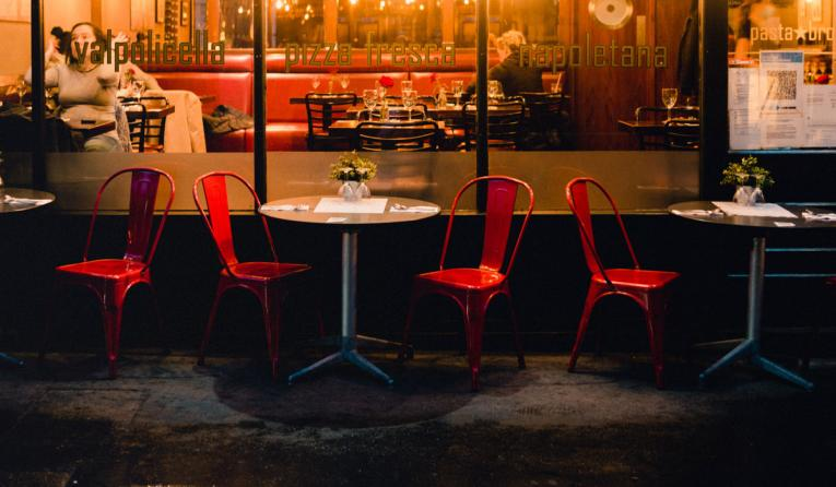 Red chairs outside a restaurant at night.