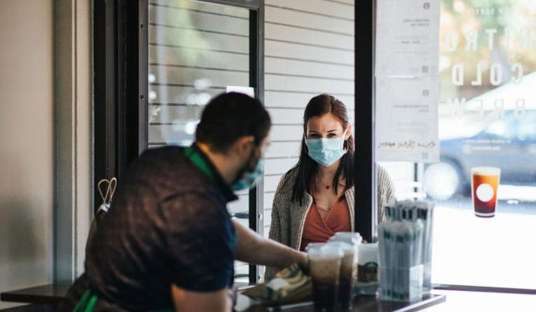 Starbucks customer wearing a mask picks up a drink.