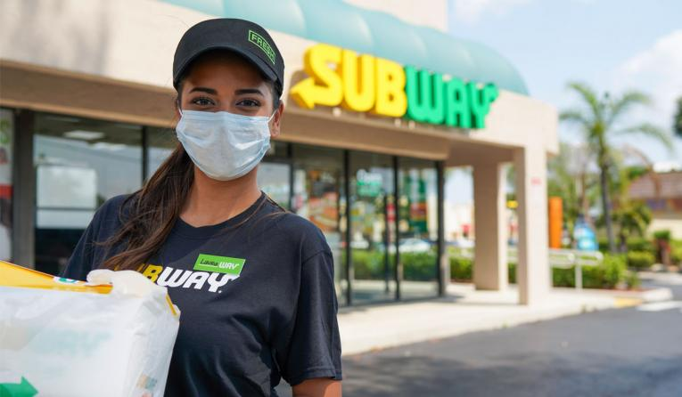 Subway employee standing outside with mask.