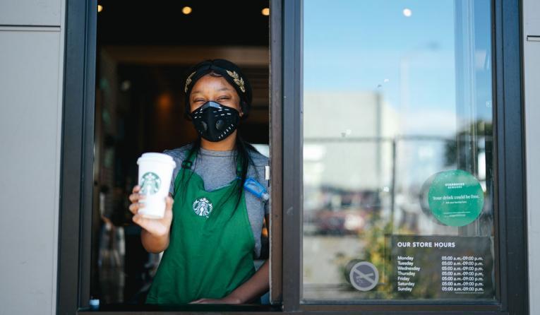 Starbucks drive-thru employee at the window.