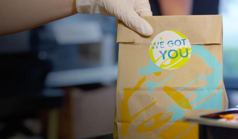 """Taco Bell bag of food with a """"we got you"""" sticker on it."""