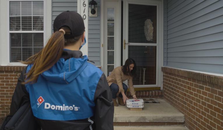 Domino's delivery driver drops off a pizza.