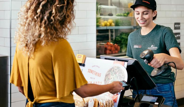 Noodles & Company employee rings up a customer.