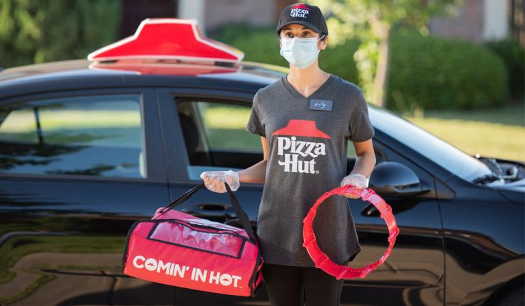 Pizza Hut employee carrying a pizza for delivery.