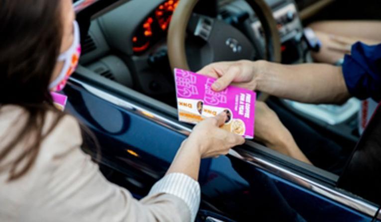 Dunkin' employee handing a card to a guest.