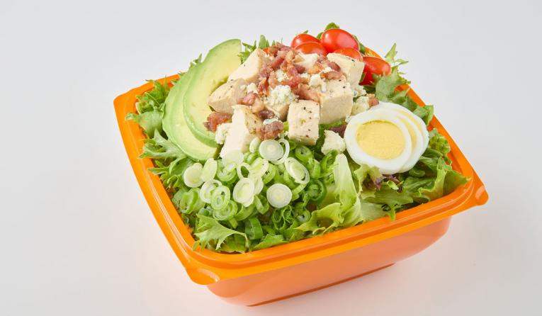 Salad and Go salad in an orange bowl.