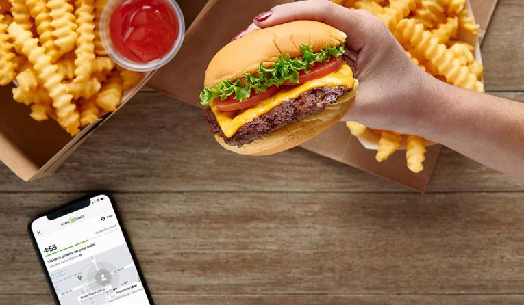 Shake Shack burger in front of a phone with the app open.