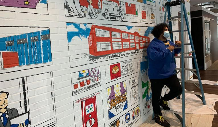 White Castle workers stands by a painted wall.