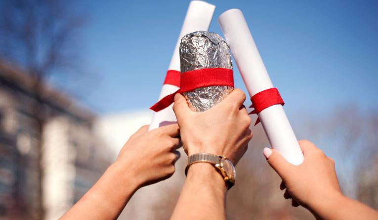 Chipotle grads hold up a burrito.