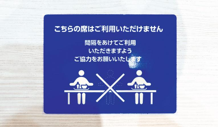 COVID-19 pandemic instruction sticker on a restaurant table in Japan