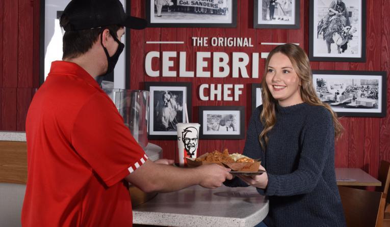 KFC employee serving a customer.