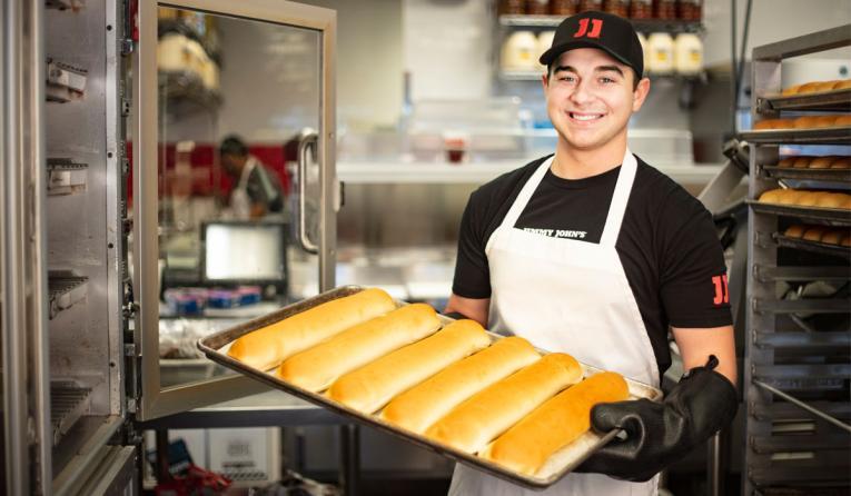Jimmy John's employee holding bread