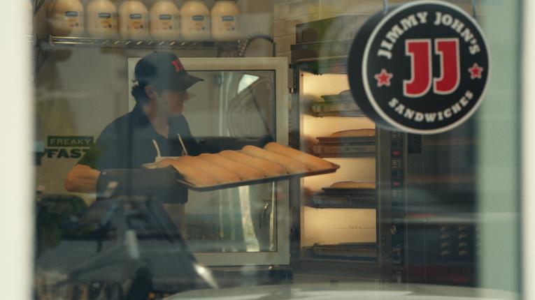 Jimmy John's employee carrying bread.